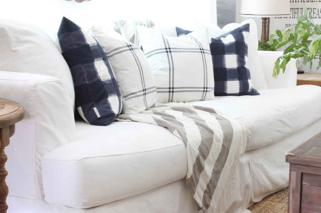 White Slipcovered sofa, with pops of blue in a relaxed, farmhouse style living room